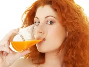 Девушка пьет морковный сок