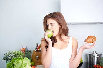 Красивая девушка ест яблоко