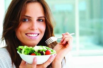 Девушка ест салат вилкой