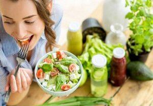 Девушка ест свежий салат из овощей