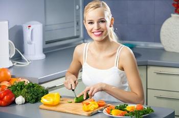 Девушка на кухне готовит овощной салат