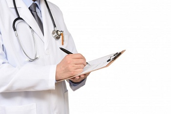 Доктор в белом халате делает записи в карте