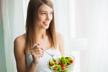 Молодая красивая девушка ест салат из овощей