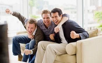 Мужчины смотрят футбол, сидя на диване