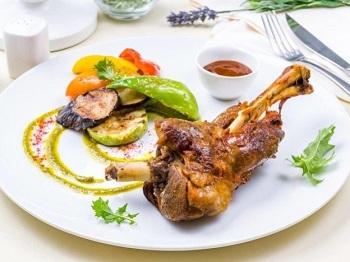 Мясо на косточке с соусом и овощами