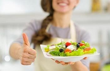У девушки в руках тарелка с салатом