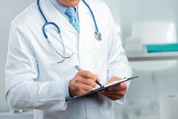 Врач заполняет медицинскую карту пациента